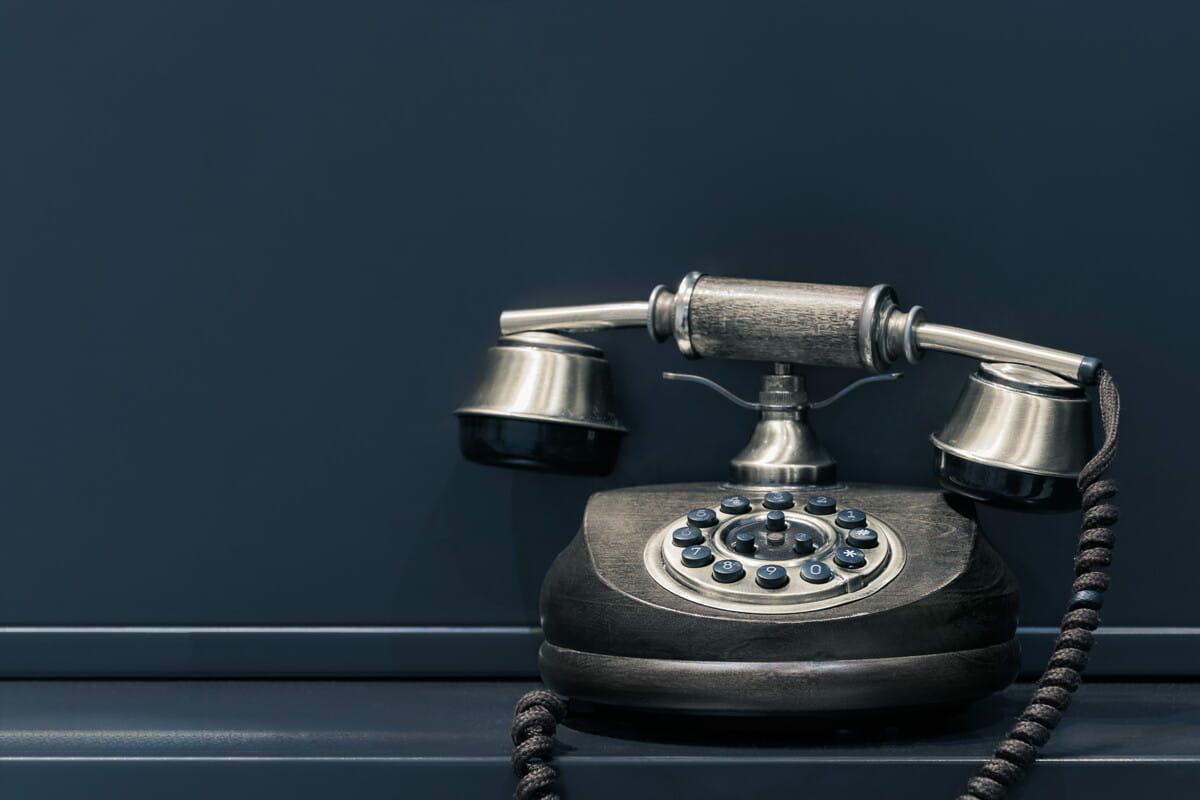 black and brown rotary phone near gray wall.jpg