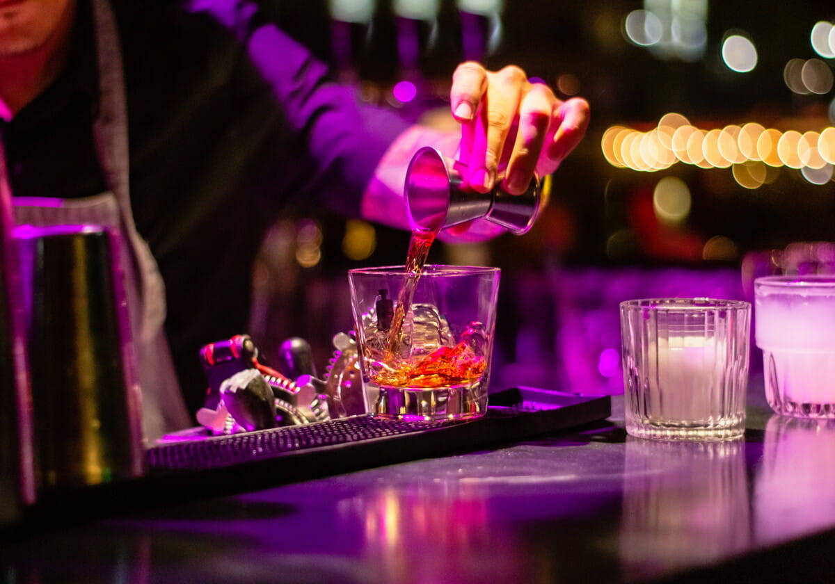 person pouring liquor in clear drinking glass.jpg