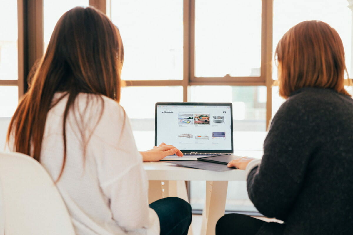 two women talking while looking at laptop computer.jpg