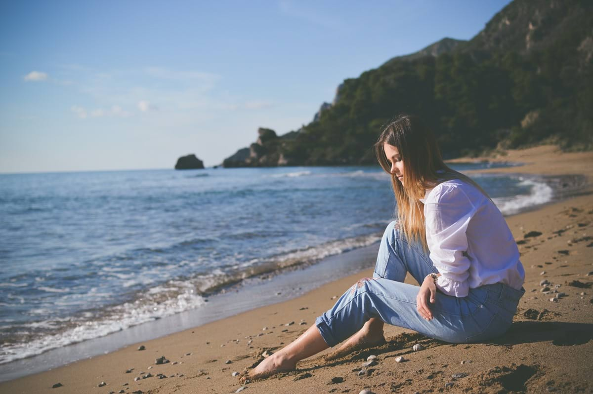 woman sitting on beach shore during daytime.jpg