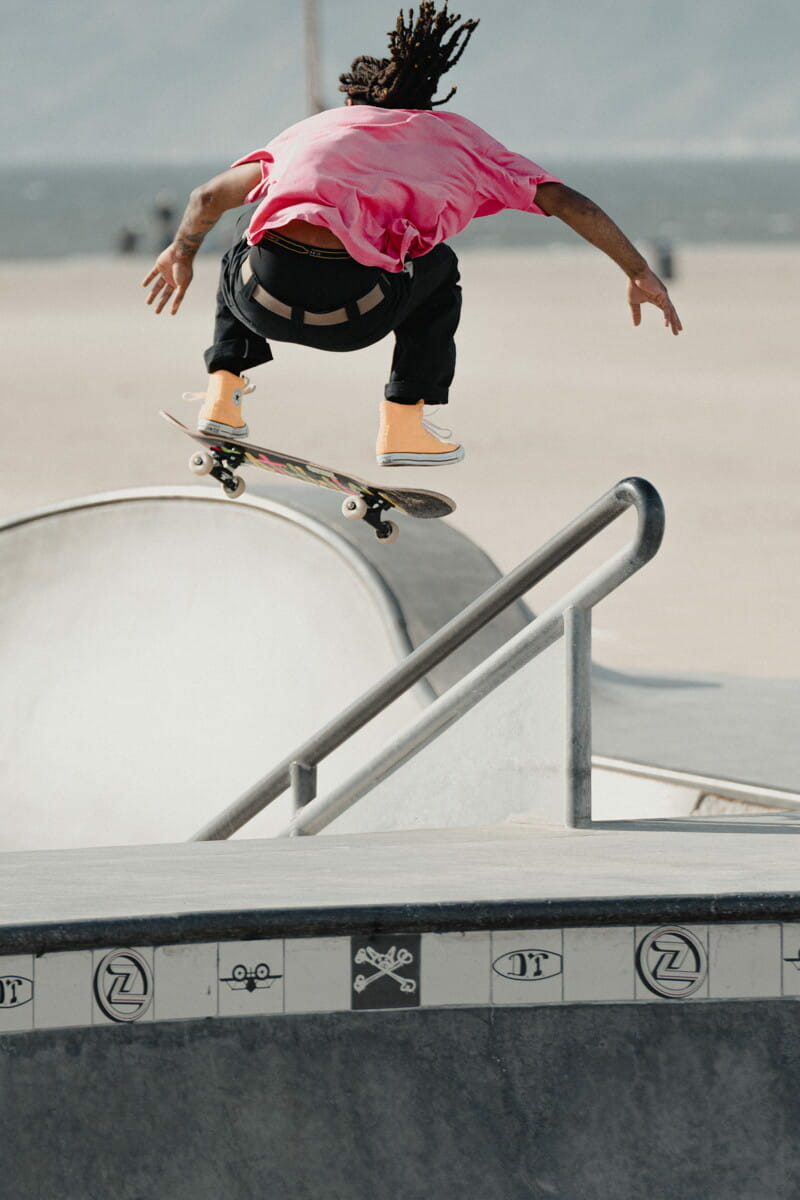 man in red and black shirt and blue shorts doing skateboard stunts.jpg