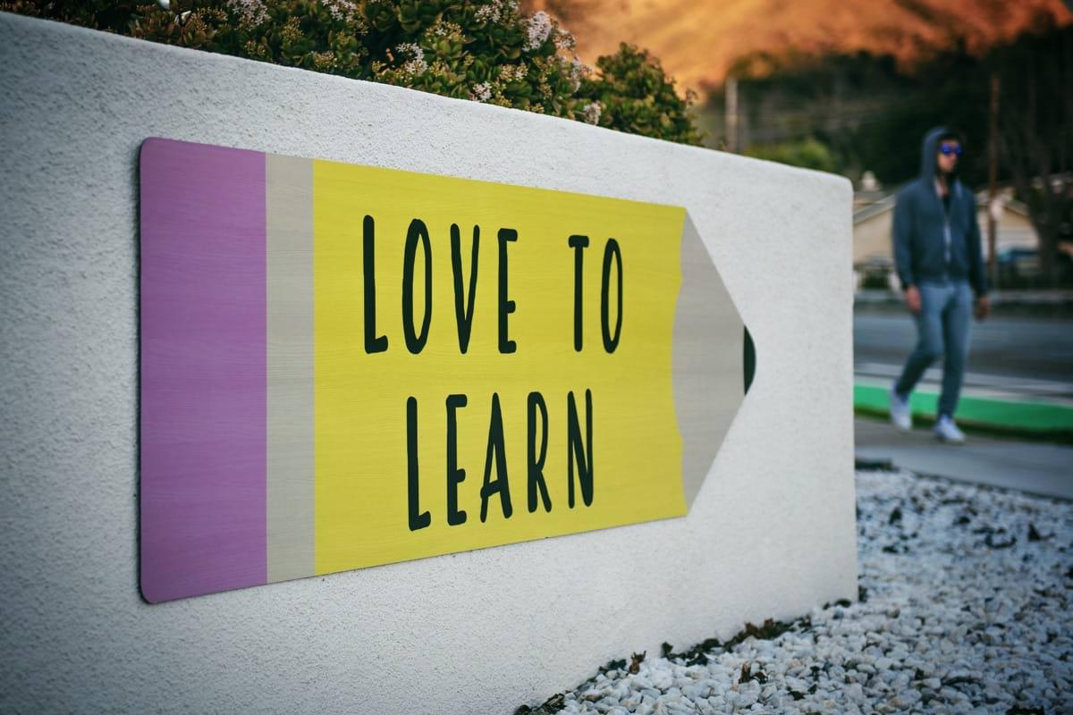 love to learn pencil signage on wall near walking man.jpg