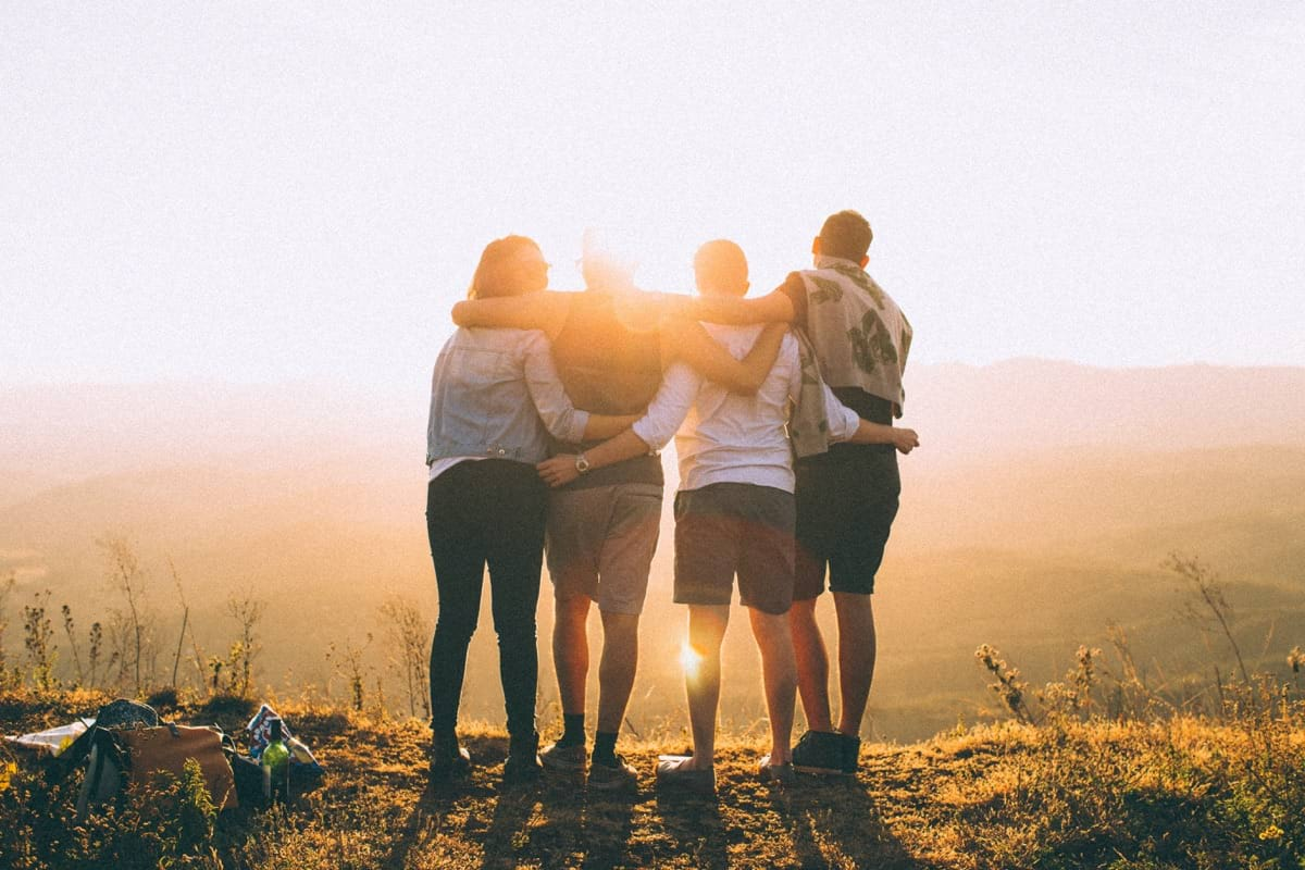 four person hands wrap around shoulders while looking at sunset.jpg