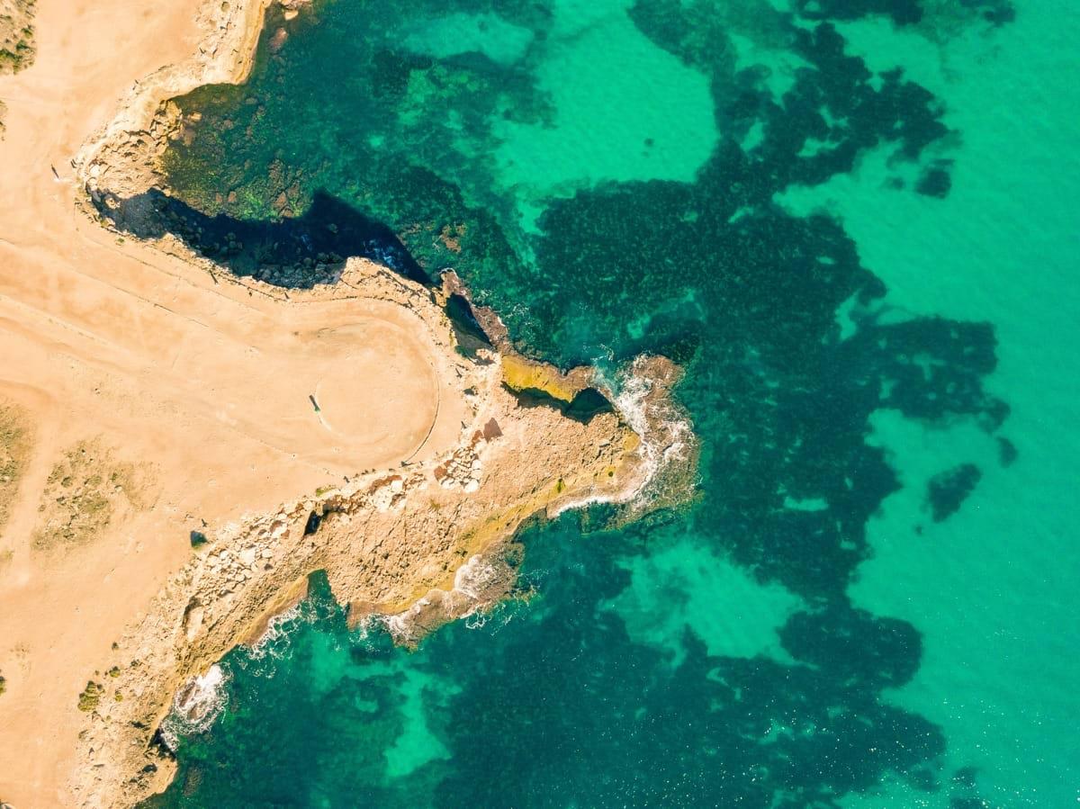 aerial photo of body of water beside brown dirt.jpg