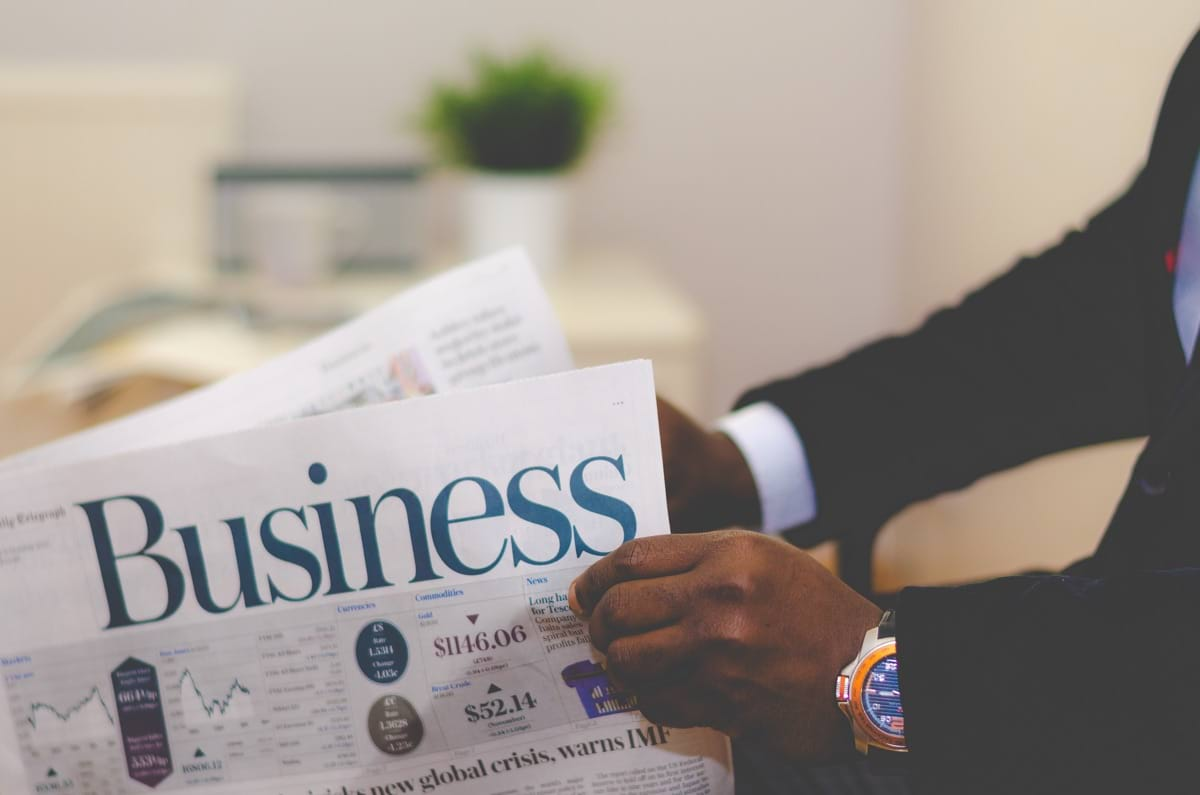 person wearing suit reading business newspaper.jpg